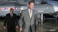 Defence Minister Peter MacKay and Industry Minister Tony Clement walk past a F-35 Joint Strike Fighter mock-up during a procurement announcement in Ottawa on July 16, 2010. (CHRIS WATTIE/REUTERS)
