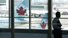 A person walks by Air Canada planes at Toronto Pearson International Airport on Friday, April 13, 2012. (Michelle Siu/THE CANADIAN PRESS)