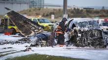 Crews attend to a plane crash at the foot of a Vancouver International Airport runway in Richmond, B.C. on Oct. 27, 2011. (John Lehmann/The Globe and Mail)