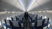 A Boeing's employee walks down the aisle of a Boeing 737-900ER seen on display at the Farnborough International Airshow, July 10, 2012. (Sang Tan/AP)