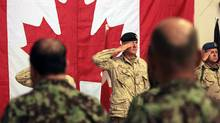 Brig.-Gen Dean Milner center, Commander of Canadian Forces Kandahar slaute along with others for Afghan and Canadian anthem during a transfer of command authority ceremony in Kandahar airbase in Afghanistan, Thursday, July 7, 2011. (Rafiq Maqbool/AP)
