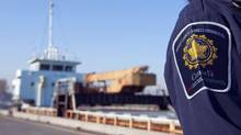 A Canadian Border Services Agent stands next to migrant ship MV Ocean Lady, which brought dozens of Tamil migrants into the country. A British Columbia judge has dismissed human smuggling charges against four men accused of bringing them into the country. (RICHARD LAM/REUTERS)