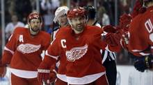 Detroit Red Wings centre Henrik Zetterberg, of Sweden, is congratulated by teammates after his second goal during the first period of an NHL game against the St. Louis Blues in Detroit, Friday, Feb. 1, 2013. (Carlos Osorio/AP)