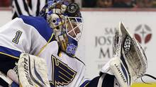 St. Louis Blues goalie Brian Elliott stops a shot as the puck hits his helmet in the second period of an NHL hockey game against the Detroit Red Wings in Detroit, Sunday April 7, 2013. St. Louis won 1-0. (Associated Press)