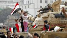 Young girls wave Egyptian flags atop an armored vehicle just outside Tahrir or Liberation Square in Cairo, Egypt, Tuesday, Feb. 1, 2011. (Victoria Hazou/AP/Victoria Hazou/AP)