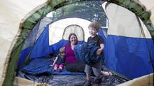 Four year old Dante carries a sleeping bag into their tent as mom Kerrie Palmer , and two year old sister Rose, look on. (Christinne Muschi/Christinne Muschi for The Globe and Mail)