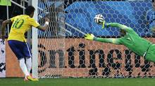 Brazil's Neymar, left, scores his sides second goal from the penalty spot during the group A World Cup soccer match between Brazil and Croatia, the opening game of the tournament, in the Itaquerao Stadium in Sao Paulo, Brazil, Thursday, June 12, 2014. (Associated Press)
