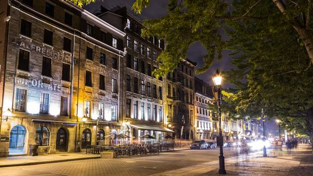 A view of buildings along Rue de la Commune in Old Montreal at night.