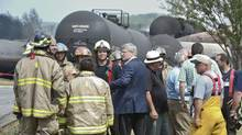 Prime Minister Stephen Harper talks with firefighters on July 7, 2013, in Lac-Mégantic, Que., on a tour of the area the day after a train derailed and exploded in the centre of town. (Paul Chiasson/The Canadian Press)