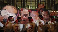 Protesters in support of Hong Kong dock workers strike deface portraits of, left to right, Hong Kong's Secretary for Labour and Welfare Department Matthew Cheung, tycoon Li Ka-shing, Mr. Li's son Victor and Hong Kong Chief Executive Leung Chun-ying, on Friday. (REUTERS)