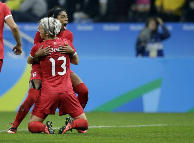 Canada's Sophie Schmidt celebrates with teammate Canada's Ashley Lawrence after scoring her team's first goal during a quarter-final match of the women's Olympic football tournament between Canada and France in Sao Paulo, Brazil, on August 12, 2016.