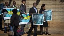 A group of wellwishers carrying get-well placards arrive at the Mediclinic Heart Hospital where former South African President Nelson Mandela is being treated in Pretoria, June 16, 2013. (Ben Curtis/AP)