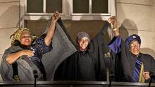 Nobel Peace Prize winners, from left, Liberian peace activist Leymah Gbowee, Tawakkol Karman of Yemen, and Liberian president Ellen Johnson-Sirleaf hold hands in solidarity from the balcony of the Grand Hotel during a torchlight procession in their honor in Oslo, Norway, Dec. 10, 2011. (Fredrik Varfjell/AP/Fredrik Varfjell/AP)