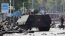 "A Thai armoured vehicle and a soldier approach a barricade during an operation to evict anti-government ""red shirt"" protesters from their encampment in . Caren Firouz/Reuters (CAREN FIROUZ)"