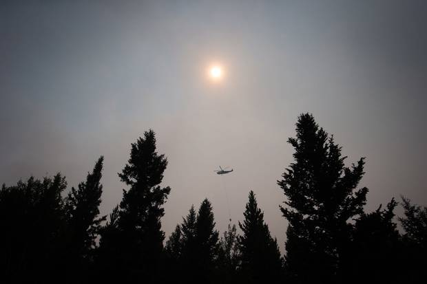 July 8, 2017: Smoke obscures the sun as a helicopter carrying a bucket battles the Gustafsen wildfire near 100 Mile House, B.C.