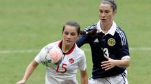 Canada's Jessie Fleming, left, fights for the ball against Scotland's Caroline Weir during the third place soccer match at the International Women's Football Tournament in Brasilia, Brazil, Sunday, Dec. 22, 2013. (Eraldo Peres/AP)