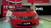 Models pose next to a G3R, a car by Chinese automaker BYD Auto, at the Guangzhou Autoshow on Dec. 20, 2010. (TYRONE SIU/TYRONE SIU/REUTERS)