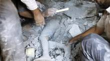 A body of a boy, who was killed by a recent Syrian Air force air strike, is seen under rubble of a house in the village of Tel Rafat, about 37 kilometres north of Aleppo, August 8, 2012. (GORAN TOMASEVIC/REUTERS)