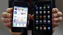Apple Inc.'s iPhone 4 smartphone, left, compared to a Samsung Electronics Galaxy S II smartphone. (Jo Yong Hak/REUTERS)