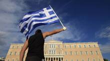 A protester raises Greek flag in front of the parliament in Athens. (© Pascal Rossignol / Reuters/REUTERS)