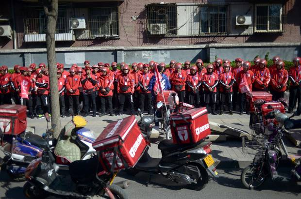 A group of food delivery drivers line up as they prepare for work along a street in Beijing.