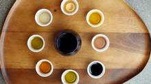 A Frantoio olive oil sits in a cobalt blue glass. It's surrounded by – from clockwise bottom, Leccino, Chipotle, Koroneiki, Cara Cara Orange Vanilla, Honey Ginger, Blood Orange, Cranberry pear, and traditional dark balsamic at Olive the Senses. (Chad Hipolito/The Globe And Mail)