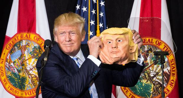 Donald Trump holds up a mask of himself at the Sarasota Fairgrounds in Sarasota, Fla., on Nov. 7, 2016.