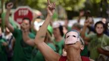 Members of the Mortgage Victims' Platform (PAH), some wearing masks with the images of Jose Antonio, who is due to be evicted, protest against evictions, in Barcelona, Spain, Friday, June 7, 2013. Spain has been in recession for the best part of the past four years as the economy battles to recover from the collapse of its once-booming real estate sector. The total number registered as jobless stands at 4.89 million. (Manu Fernandez/AP)