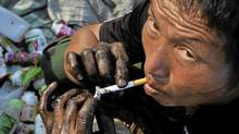 A migrant worker lights up a cigarette as he takes a break at a garbage dump site in Taizhou, Zhejiang province, Aug. 2, 2011. (Reuters/REUTERS)