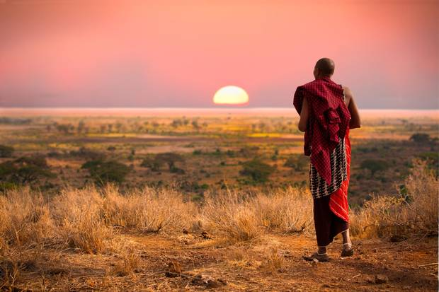 A Masai man, wearing traditional blankets, looks out over the Serengeti in Tanzania as the colorful sunset fills the sky.