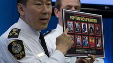 Vancouver Police Chief Jim Chu holds up a poster of the VPD's most wanted during a news conference in Vancouver, Tuesday, June 12, 2012. Those on the most wanted poster are people who were involved in the June, 2011 hockey riots. (JONATHAN HAYWARD/THE CANADIAN PRESS)
