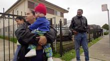 Sindia Lozada, left, holds Josue Ramirez, her neighbour's son, as Frank Gilbert looks on in Oakland, Calif., in a file photo. The latest U.S. census reveals that real median household income remains 8.3 per cent below its level in 2007, the year before the recession began. (MARCIO JOSE SANCHEZ/AP)