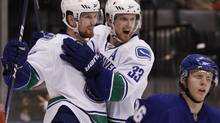 Vancouver Canucks' Daniel Sedin (L) celebrates his goal with his twin brother Henrik Sedin behind Toronto Maple Leafs' Carl Gunnarsson during the third period of their NHL hockey game in Toronto January 30, 2010. REUTERS/Mark Blinch (MARK BLINCH)