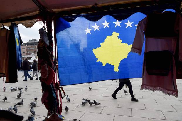 A pedestrian walks behind Kosovo flag displayed in Pristina on February 13, 2018, ahead of the tenth anniversary of Kosovo independence. Kosovo unilaterally declared independence from Serbia on February 17, 2008 and since has been recognized as a state by more than 110 countries, despite Belgrade's fierce opposition.