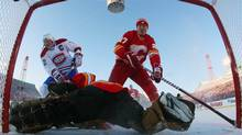 Calgary Flames' alumni goalie Mike Vernon makes a save on Montreal Canadiens' alumni Mike Keane while Flames' Brian MacLellan watches the puck during the first period of their NHL Heritage Classic alumni hockey game in Calgary, Alberta, February 19, 2011. (Reuters)