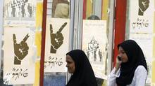 An August 2007 file photo shows women walking past electoral posters towards a polling station in Male, Maldives. (ANURUDDHA LOKUHAPUARACHCHI/REUTERS)
