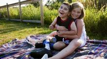 Jillian Smigielski, 10, holds her eight-year-old brother Ryan Smigielski, who suffered brain damage after a hypoglycemic attack four years ago. (MICHELLE SIU FOR THE GLOBE AND MAIL)