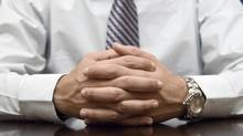 Close up of a businessman's hand clasped on his desk. (Royal Five/© Jared DeCinque 2008)