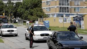 Toronto Police officers stop a car on Grenoble Dr., the street where Dianthony Evans was killed in Flemingdon Park
