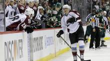 Colorado Avalanche defenseman Tyson Barrie, right, leaves the ice after being hit by Minnesota Wild left wing Matt Cooke during the second period of Game 3 of an NHL hockey first-round playoff series in St. Paul, Minn., Monday, April 21, 2014. The Wild won 1-0 in overtime. (Ann Heisenfelt/THE ASSOCIATED PRESS)