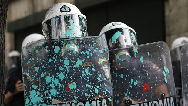 Riot police shields are splattered with paint thrown by protesters during a protest in front of the parliament in Athens on Oct. 9, 2012 as German Chancellor Angela Merkel makes her first visit to Greece since the eurozone crisis began here three years ago. Her five-hour stop is seen by the government as a historic boost for the country's future in Europe's shared currency, but by protesters as a harbinger of more austerity and hardship. (Lefteris Pitarakis/AP)