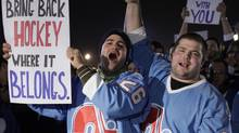 Fans of the Quebec Nordiques hold signs outside the location where an NHL hockey game between the New York Islanders and the Atlanta Thrashers is being held in Uniondale December 11, 2010. The fans had gathered to show that their city Quebec should have an NHL team of their own. The Quebec Nordiques last played in the NHL 15 years ago. REUTERS/Chip East (CHIP EAST)