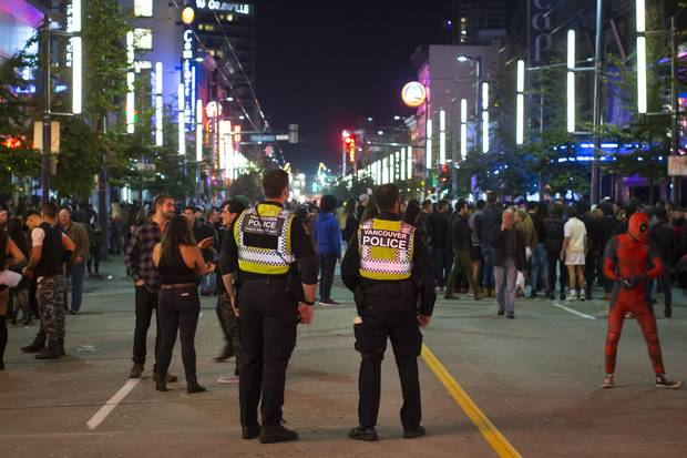 Police officers watch over the crowd on Granville Street in Vancouver.