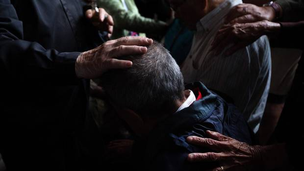Father Bernie Black and other believers lay hands on people as they pray at Lac Ste Anne, Alberta on Wednesday, July 22, 2015.
