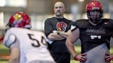 University of Calgary Dinos head coach Blake Nill, centre, looks on during a practice in preparation for the Vanier Cup on Wednesday. (JACQUES BOISINNOT/THE CANADIAN PRESS)