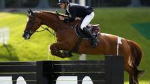 Pieter Devos of Belgium jumps on his horse Candy to a first-place finish at the CN International Grand Prix trophy during the Spruce Meadows Masters in Calgary, Alberta, September 8, 2013. (TODD KOROL/REUTERS)