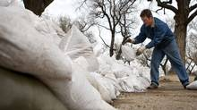 Colder temperatures have helped ease the threat of flooding but residents are taking nothing for granted and are preparing for the worst as flood waters threaten homes and businesses in Medicine Hat, Alta., Thursday, April 14, 2011. David Stickel, an employee of Saamis Funeral Home, was busy sand bagging the perimeter of the business. Much of southeastern Alberta and southwestern Saskatchewan is under flood watch warnings. (Jeff McIntosh/The Canadian Press/Jeff McIntosh/The Canadian Press)