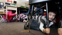 "Grade one student Joseph Kim, 6, takes cover under his desk during an earthquake drill at Hollyburn Elementary School in West Vancouver, B.C., January 26, 2011. More than 400,000 British Columbians took part in the drill called ""ShakeOut"" simultaneously at schools and businesses across the province in the largest earthquake-preparedness program ever held in Canada. (DARRYL DYCK/THE CANADIAN PRESS)"