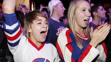 Taylor Mecleiros and Lisa Meissner listen to Bachman and Turner at the NHL Face-off party at The Forks in Winnipeg, Thursday, October 6, 2011. THE CANADIAN PRESS/Winnipeg Free Press-John Woods (John Woods/CANADIAN PRESS/Winnipeg Free Press)