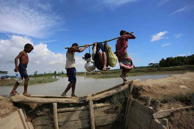 """Abdur Sabur and Mohammad Enayatullah carry their elderly uncle into Bangladesh, after picking him up in Myanmar, where Mr. Sabur said he saw """"rivers of blood."""" Soldiers in Myanmar also opened fire on them."""